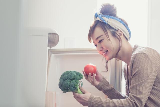 久しぶりに料理したくて冷蔵庫から食材を取り出した女性