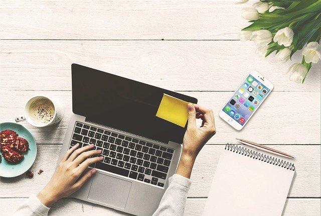 パソコンと携帯電話を使っている人の画像