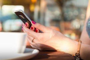 携帯電話を手に取る女性