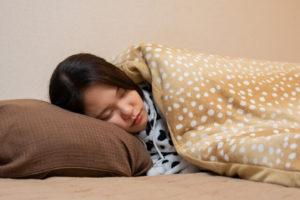 疲れてベッドで眠る女性