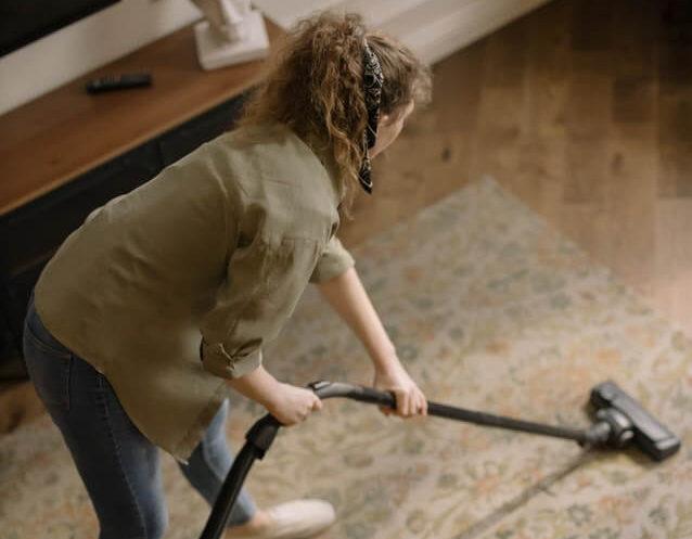 部屋の掃除機する女性