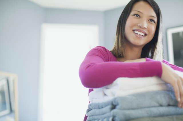 洗濯物をたたんでしまう女性