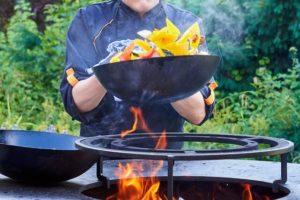 鉄のフライパンで調理している男性