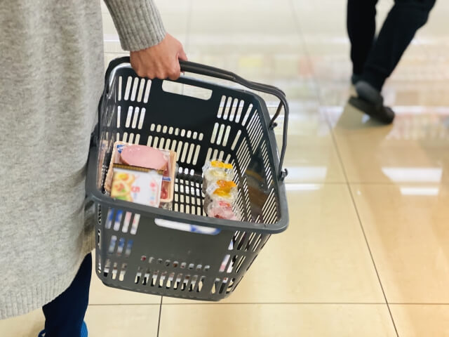 スーパーの買物カゴに食品を入れる女性