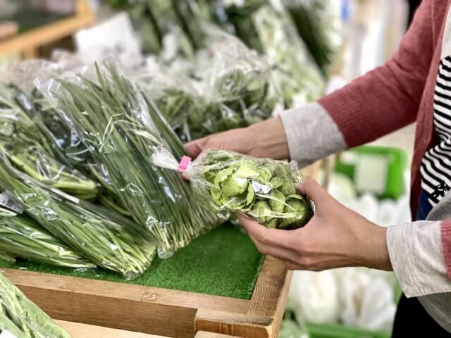 スーパーで野菜を選ぶ女性
