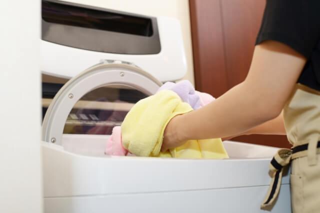 夫を送り出してから洗濯する女性