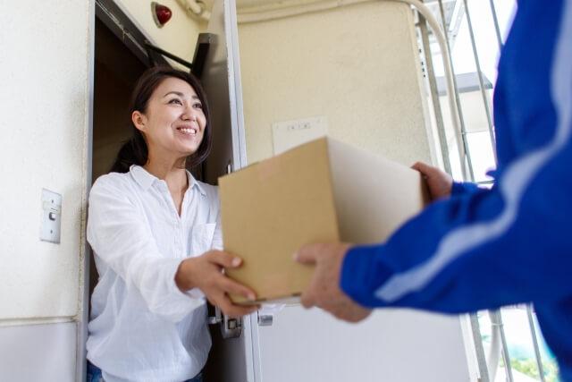 宅配業者から荷物を受け取る女性