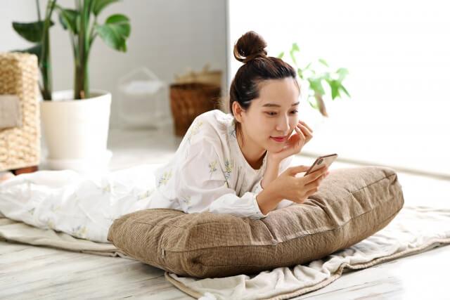 自宅で寝そべって携帯を見る女性